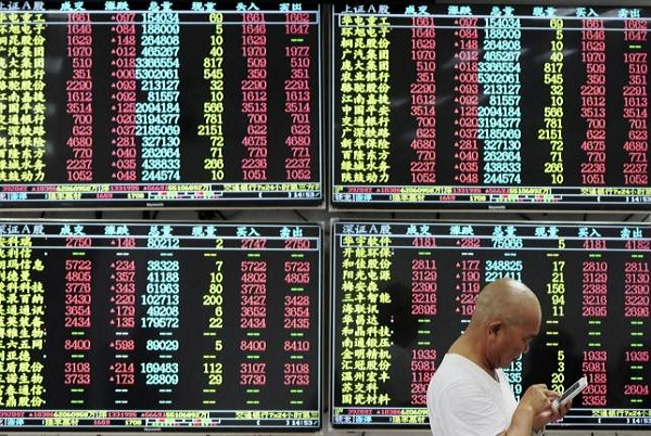 An investor looks at his mobile phone in front of electronic screens showing stock information at a brokerage house in China