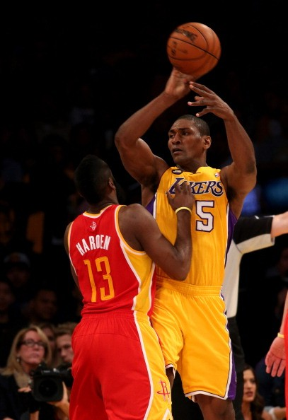 Metta World Peace of the Los Angeles Lakers throws a pass over James Harden #13 of the Houston Rockets at Staples Center on April 17, 2013 in Los Angeles, California.
