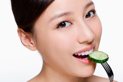 The image features the woman eating pickles as a means to maintaining her glow naturally.