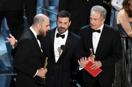 """The """"La La Land"""" producer Jordan Horowitz on the left announces that """"Moonlight"""" is the Oscars Best Picture winner. Horowitz is with the host Jimmy Kimmel, in the middle and with the actor Warren Beatty on the right."""