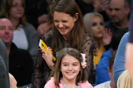 The image depicts Katie Holmes and Suri Cruise.