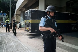 Hong Kong police officers stand guard around a prison vehicle.