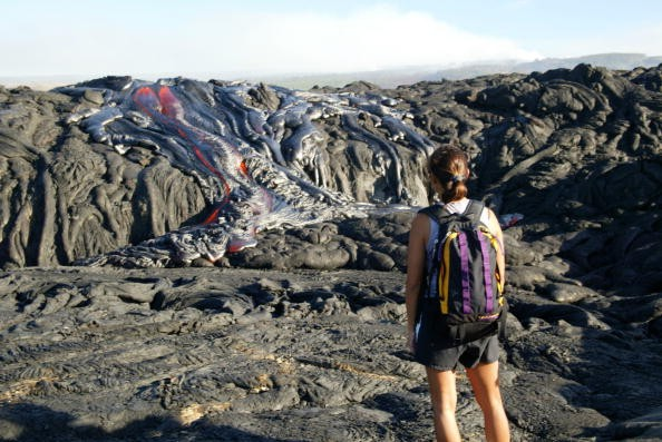 Hiker Gigi Galong, of Kona, watches the lava flow in Volcano National Park. On July 27 Kilauea's lava flow increased resulting in additional forest fires within the park